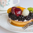 Mini fruit tart with tea - Stock Photo