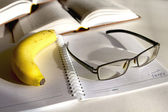 Banana and glasses on a notepad — Stock Photo
