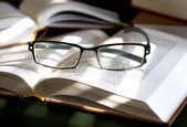 Open books with glasses resting on them — Stock Photo