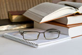 Pilha de livros com o bloco de notas e óculos — Foto Stock