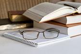 Stapel boeken met kladblok en glazen — Stockfoto