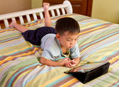 Chinese boy using tablet while lying on bed — Stock Photo
