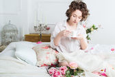 Beautiful girl wakes up and drinks coffee — Stock Photo