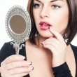 Beautiful brunette girl looks in mirror — Stock Photo