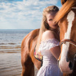Beautiful blonde woman and a horse — Stock Photo