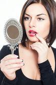 Mooie brunette meisje kijkt in spiegel — Stockfoto
