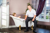 Portrait of married couple having bath with glass of champagne — Stock Photo