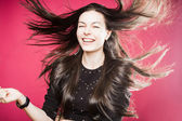 Portrait of pretty young woman with flying hair and smile — Stock Photo