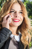Portrait of beautiful smiling young woman talking on the phone — Stock Photo