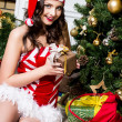 Beautiful young woman in Santa Claus clothes holding presents over Christmas background. — Stock Photo #45769171