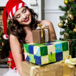 Beautiful young woman in Santa Claus clothes holding presents over Christmas background. — Stock Photo #45769173