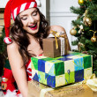 Beautiful young woman in Santa Claus clothes holding presents over Christmas background. — Stock Photo #45769179