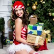 Beautiful young woman in Santa Claus clothes holding presents over Christmas background. — Stock Photo #45769185