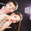 Funny young man and woman peeking around the corner of image — Stock Photo #45769357