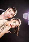 Funny young man and woman peeking around the corner of image — Stock Photo