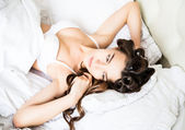 Beautiful bride in white lingerie lying on the bed in her bedroom in a morning — Stock Photo