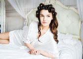Beautiful bride in white silk lingerie lying on the bed in her bedroom in a morning — Stock Photo