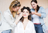 Stylist and makeup artist preparing bride before the wedding in a morning — Stock Photo