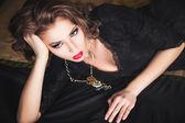 Szczegół portret seksowny Ciemnowłosa dziewczyna w czarnej sukni, pozowanie na łóżku — Zdjęcie stockowe