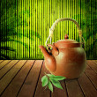 Royalty-Free Stock Photo: Teapot on a wooden table with bamboo background.