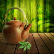 Teapot on a wooden table with bamboo background. - Stock Photo