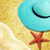 A turquoise straw hat on the sand beach. — Stock Photo