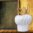 Chef hat on kitchen table — Stock Photo #25090151