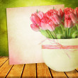 Beautiful pink tulips in a vase on a wooden table — Stock Photo