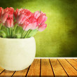 Beautiful pink tulips in a vase on a wooden table  — Stok fotoğraf