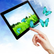 Digital tablet PC like ipade and woman hand pointing over blue sky background. — Stock Photo