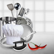 Cook hat, pile of pots and pans on the kitchen background. — Stock Photo