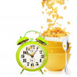 Alarm clock and golden cornflakes falls into the stack of yellow bowls — Stock Photo #26193815