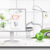 Computer and green apple on the table in dental office. — Stock Photo