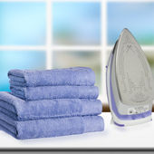 Pile of towels and smoothing-iron. — Stock Photo