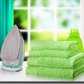 Pile of towels and smoothing-iron . — Stock Photo
