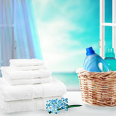Pile of towels and liquid laundry detergent on the table. — Stock Photo