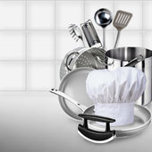 Cook cap, pile of pots and pans on the kitchen background. — Stock Photo
