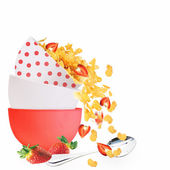 Golden corn flakes with strawberries spill out of the bowl — Stock Photo