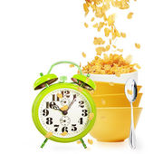 Alarm clock and golden cornflakes falls into the stack of yellow bowls — Stock Photo