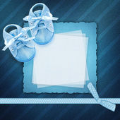 Blank card with baby shoes on blue background — Stock Photo