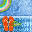 Flip flops near tropical swimming pool — Stock Photo #27247361