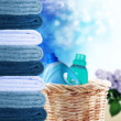Pile of towels and liquid laundry detergent on sunny sky background — Stock Photo #28009893