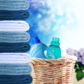 Pile of towels and liquid laundry detergent on the sunny sky background — Stock Photo