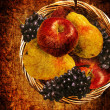 Fruits in the basket on grunge background, vintage or antique look. — Stock Photo
