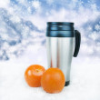 Thermos travel tumbler and oranges on the winter background. — Stock fotografie