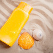 Stock Photo: Sunblock lotion and seashells on sand beach background.