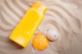 Sunblock lotion and seashells on sand beach background. — Stock Photo