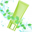 Cream tube with green leaves. — Stock Photo