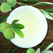 Closeup of jar of moisturizing face cream and twig with green olives. — Stock Photo