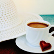 Cup of coffee with small red chocolate in shape of heart on the sea background  — Stock Photo